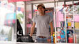 Image:  A man stands at the register in a carnival cart