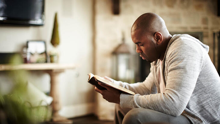 man reading bible in his home
