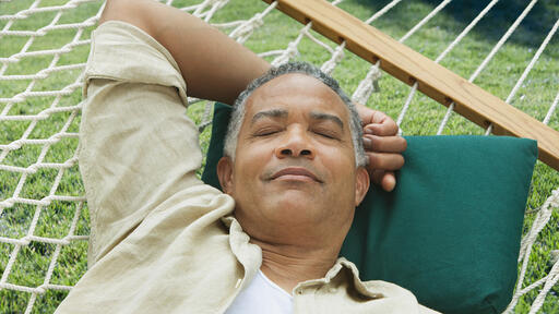 Image of a man lounging on a hammock in the summer.