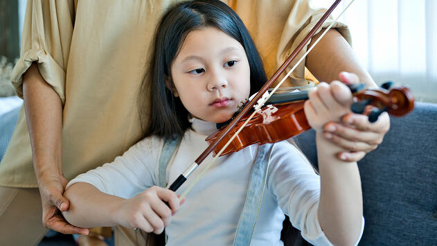 A young girl being taught to play violin.