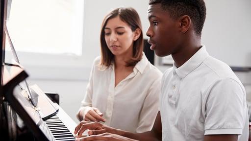 A piano teacher helping a student