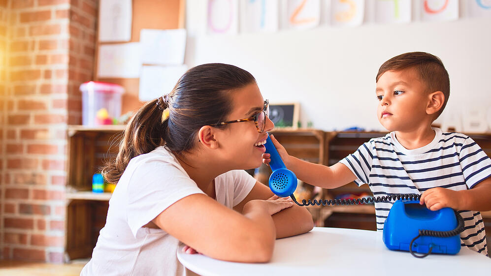 A woman and child playing with a telephone.