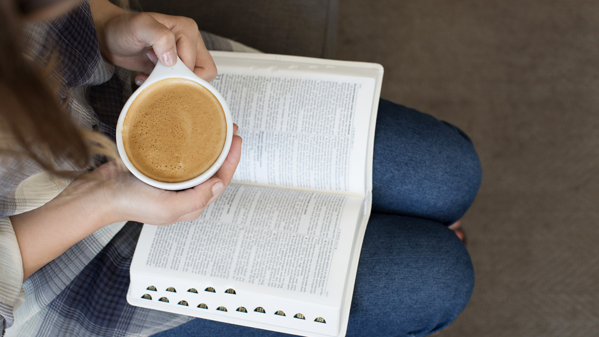 woman-with-bible-open-on-lap-and-holding-a-cup-of-coffee